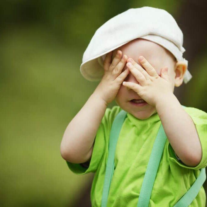 little boy plays hide and seek